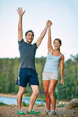 Happy couple raising arms — Stock Photo