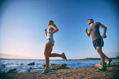 Couple running down coastline — Stock Photo