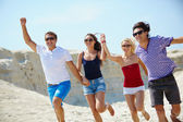 Young people running down sandy beach — Stock Photo