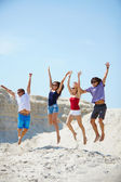 Young people  jumping over sandy beach — Stock Photo
