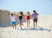 Young people running on the sand — Stock Photo
