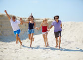 Young people running down beach — Stockfoto