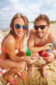 Lovers on the beach with cocktails — Stock Photo