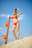 Girl posing with snowboard on the beach — 图库照片