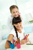 Girl and mother with colorful pencils — Photo
