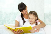 Girl and her mother reading book — Stock Photo