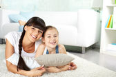 Girl and her mother resting at home — Stockfoto