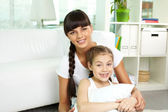 Girl and her mother resting at home — Stock Photo