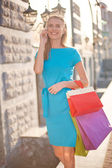 Girl with shopping bags calling — Stock Photo