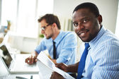 Happy businessman with colleague using laptop — Stock Photo