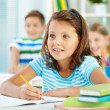 Cute girl and her two schoolmates at lesson — Stock Photo #51565587