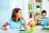 Pensive girl drawing at workplace — Stock Photo