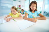 Schoolgirls drawing at workplace — Stock Photo