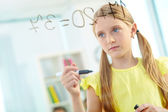 Girl doing sums on transparent board — Stock Photo