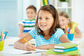 Cute girl and her two schoolmates at lesson — Stock Photo