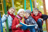 Schoolkids reading book — Stock Photo