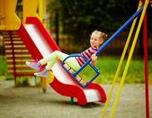 Girl swinging on playground — Stock Photo