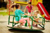 Friends having fun on carousel — Stock Photo