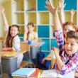 Boy raising hand at workplace with classmates — Stock Photo #51573671