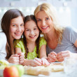 Girls and their mother cooking pastry — Stock Photo #51577725
