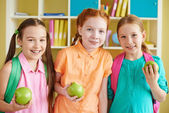 Girls with backpacks and green apples — Stock Photo