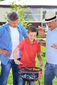 Boy frying sausages — Stock Photo
