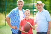 Boy with rugby ball, grandfather and father — Stock Photo