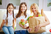 Mother and two daughters in kitchen — Stock Photo