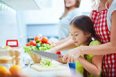 Girl helping her mother to cook — Stock Photo