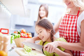 Mother and two daughters cooking — Stock Photo