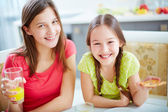 Girls sitting by dinner table — Stock Photo