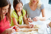 Girls and mother cooking pastry — Stock Photo