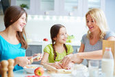 Girls helping mother to cook pastry — Stock Photo