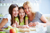 Girls and their mother cooking pastry — Stock Photo