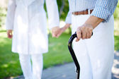 Female hand holding cane with doctor — Stock Photo