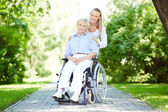 Nurse and senior patient in a wheelchair — Stock Photo