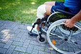 Man hand on wheel of wheelchair — Stock Photo
