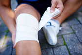 Man bandaging leg — Stock Photo