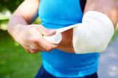 Man bandaging arm — Stockfoto