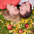 Couple lying on ground with red apples — Stock Photo #51631917