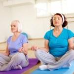 Aged females doing yoga exercise — Stock Photo #51635055