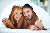 Young couple under blanket — Stock Photo