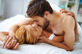 Female and male lying on bed — Stockfoto