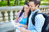 Young travelers studying map — Stock Photo