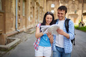Travelers looking at map — Stock Photo