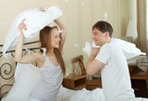 Couple playing with pillows in bed — Stock Photo
