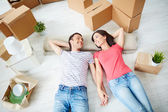 Couple lying on the floor of new house — Foto de Stock