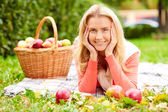 Girl with apples lying in park — Stock Photo