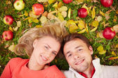 Couple with apples  lying on ground — Stock Photo