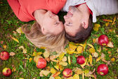 Couple  lying on ground with red apples — Stok fotoğraf
